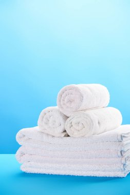 close-up view of rolled and stacked clean white towels on blue