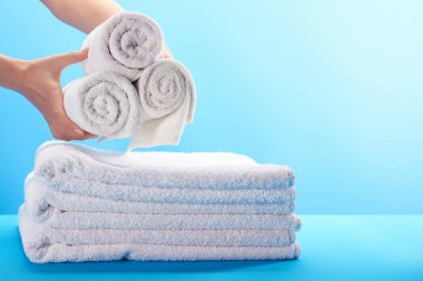 cropped shot of person holding rolled white towels above pile of towels on blue