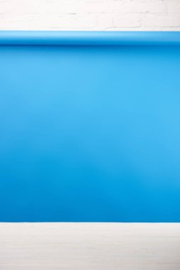 Blue background and light wooden surface at white brick wall stock vector