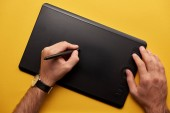 cropped shot of man drawing with graphics tablet on yellow surface