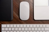 Fotografie částečný pohled laptop s bezdrátovou myší, grafický tablet a klávesnice na dřevěný stůl