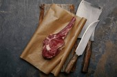 Photo top view of raw rib eye steak on baking paper with kitchen knives on grey background