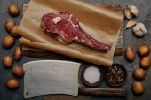 Photo flat lay with raw rib eye steak on baking paper with butcher knife, spices, potatoes and garlic
