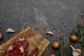 pohled shora syrové maso steak na pečícím papírem s kořením, bylinkami a brambory na šedém pozadí