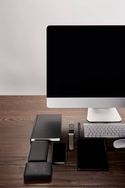 monoblock computer with various devices on wooden table isolated on grey