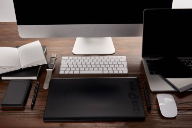 modern designer workplace with different gadgets on wooden table