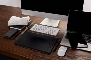 modern graphics designer workplace with different gadgets on wooden table