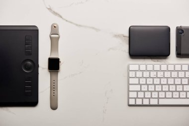 flat lay with graphics tablet with portable hdd, smart watch and wireless keyboard on white marble surface