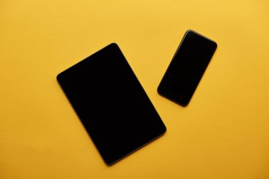 top view of tablet and smartphone on yellow surface