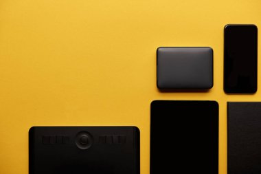 top view of graphics tablet with digital tablet, smartphone and portable hdd on yellow surface