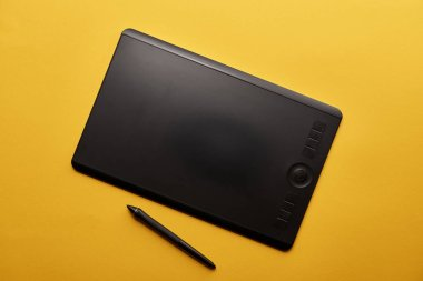 top view of graphics tablet and pen on yellow surface