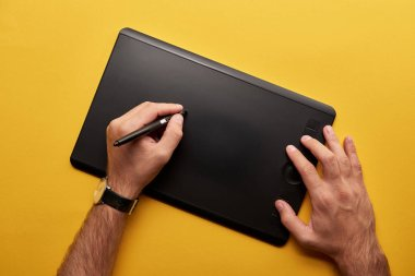 cropped shot of artist drawing with graphics tablet on yellow surface