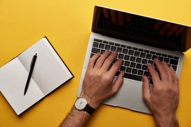cropped shot of man working with laptop and notebook on yellow surface
