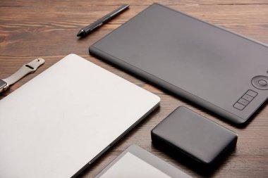 yakın çekim çekim çeşitli kablosuz cihazlar ve ahşap masa üzerinde grafik tablet