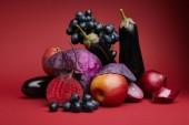 Detailní pohled čerstvých zralých hroznů, jablek, lilku, mangoldu, cibule a zelí na červené