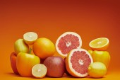 close-up view of fresh ripe citrus fruits and bell peppers on orange background