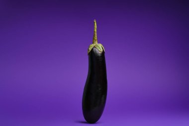 close-up view of fresh ripe organic eggplant on purple background