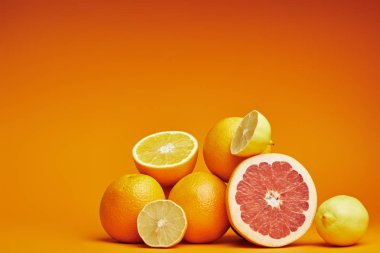 fresh ripe whole and sliced citrus fruits on orange background