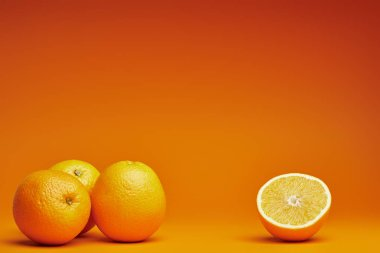 close-up view of whole and halved oranges on orange background