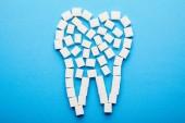 pohled shora bílého cukru kostek, které jsou uspořádány v zubu znamení na modrém pozadí, koncept zubní péče
