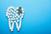 Fotografie top view of white and brown sugar cubes arranged in tooth sign on blue background, dental caries concept