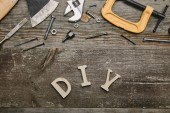 Fotografie Top view of different carpentry tools and diy sign on wooden background