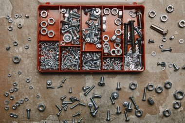Top view of box with bolts and scattered nails and screws on old background