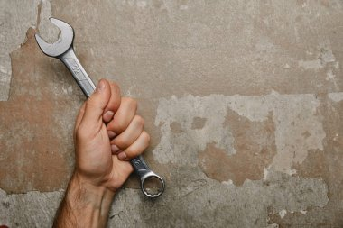Partial view of man holding wrench on old background