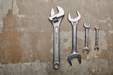 Top view of set of wrenches tools and one monkey wrench on the background of old  surface stock vector