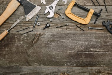 Top view of different carpentry tools on wooden background