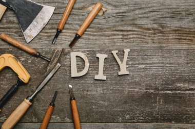 Top view of different carpentry tools and diy sign on wooden background