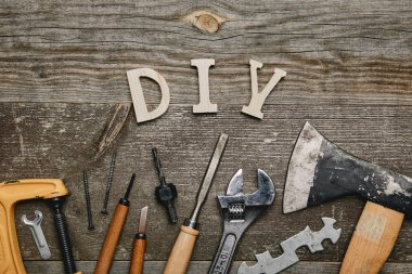 Flay lay with different carpentry tools and diy sign on wooden background stock vector