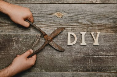 Partial view of man holding vintage rusty carpentry scissors on wooden background with diy sign
