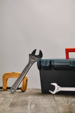 Close up of various tools on wooden table on grey background