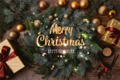 top view of Christmas gift boxes and fir wreath on wooden table with merry christmas and happy new year lettering and glowing lights