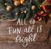 pohled shora vánoční dárkové krabičky, věnec jedle, stuha cívky a nůžek na dřevěný stůl s vše je zábava, vše je jasné inspirace