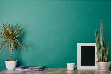 Plants, photo frame, journals and cup of beverage on green background