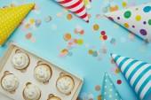 Pohled shora chutné koláčky, klobouky a barevné konfety na modrém pozadí