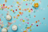 Top view of tasty cupcakes, confetti and gift on blue background