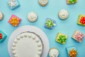 Felülnézet, finom sütemény, cupcakes és ajándékok a kék háttér