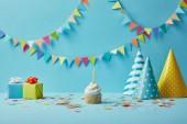 Fotografie  Lahodné košíčky, klobouky, konfety a dary na modrém podkladu s barevnými prapory