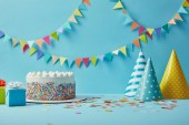 Photo Tasty cake with sugar sprinkles,party hats and gifts on blue background with colorful bunting