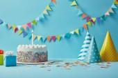 Finom születésnapi torta, ajándékok, party kalap és konfetti a kék háttér sármány