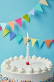 Fényképek Candle on tasty birthday cake on blue background with bunting