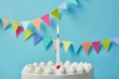 Gyertya a finom születésnapi torta a kék háttér sármány