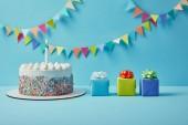 Finom torta cukor sprinkles és ajándékok a kék háttér színes sármány