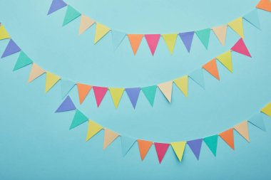 Top view of festive colorful bunting on blue background