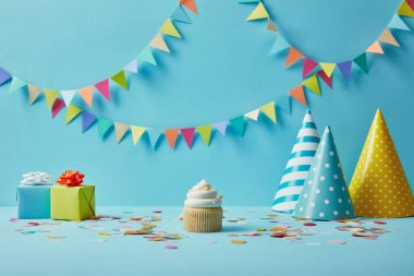 Tasty cupcake, party hats, confetti and gifts on blue background with colorful bunting stock vector