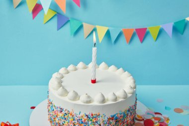 Candle on birthday cake with sugar sprinkles on blue background with bunting