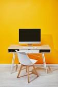 Fotografie počítač na pracovišti s židle a žluté zdi v pozadí